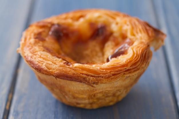 Traditionelles portugiesisches plätzchen pasteis de nata auf blauer holzoberfläche