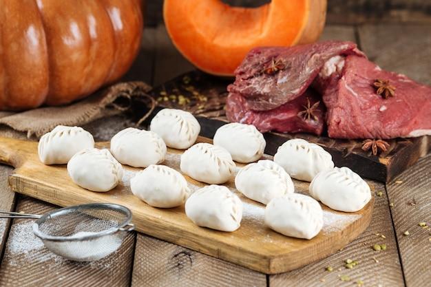 Traditionelles russisches gericht von manti-knödeln mit fleisch und kürbis