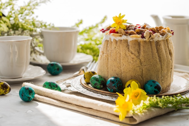 Traditionelles russisches osterhüttenkäsedessert, orthodoxes paskha auf tisch mit kulich-kuchen, blumen, farbigen eiern.
