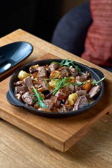 Traditionelles schweizer gericht kalbfleisch mit kartoffeln in einer cremigen sauce nahaufnahme auf einer geschmiedeten pfanne auf dem tisch