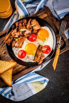 Traditionelles selbst gemachtes englisches amerikanisches frühstück, spiegeleier, toast, speck, mit kaffeetasse und dunklem hintergrund des orangensaftes, draufsicht