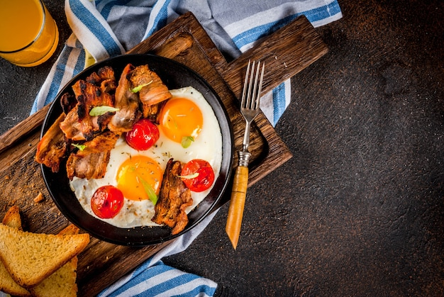 Traditionelles selbst gemachtes englisches amerikanisches frühstück, spiegeleier, toast, speck, mit kaffeetasse und dunklem hintergrund des orangensaftes, draufsichtkopienraum