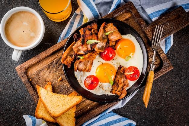 Traditionelles selbst gemachtes englisches amerikanisches frühstück, spiegeleier, toast, speck, mit kaffeetasse und orangensaft