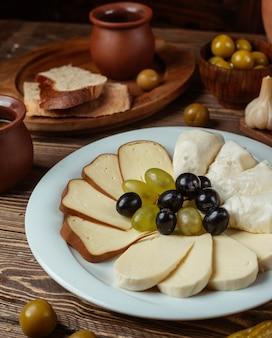 Traditionelles setup für käseplatte mit geräuchertem, weißem ziegenkäse, trauben