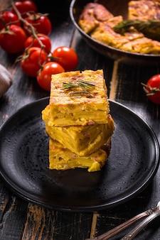 Traditionelles spanisches gericht mit knoblauchsauce aioli und frischen tomaten kirsche. omelett mit eiern, kartoffeln und zwiebeln. rustikaler schwarzer hintergrund