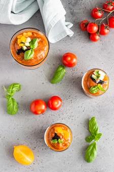 Traditionelles spanisches kaltes suppenpüree mit tomaten, gurken und basilikum garnieren