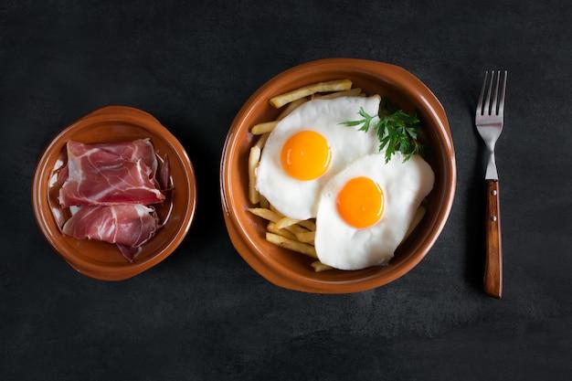 Traditionelles spanisches mittagessen - spiegeleier mit pommes frites, geräucherte schweinescheiben jamon