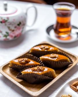 Traditionelles süßigkeiten-pakhlava-dessert mit walnüssen auf der seitenansicht des holzbretts