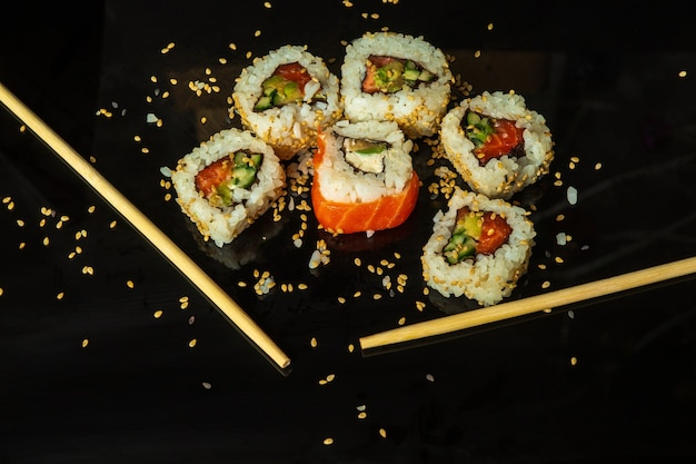 Traditionelles sushi mit sesam und stäbchen