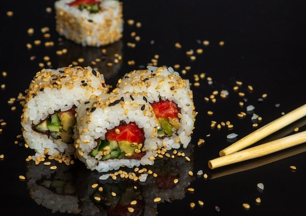 Traditionelles sushi und essstäbchen - philadelphia mit lachs, avocado und käse.