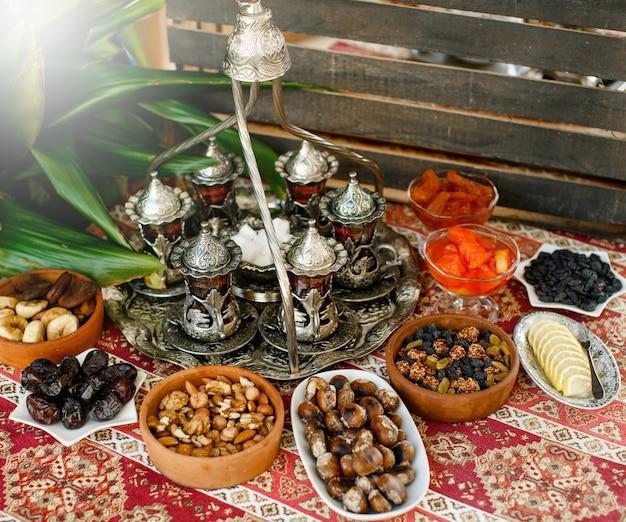 Traditionelles teesetup mit antikem teetablett und gläsern sowie trockenen obstschalen