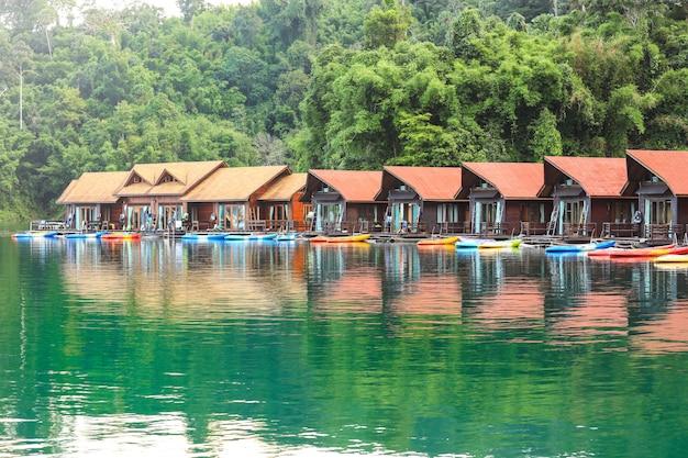 Traditionelles thailändisches bambushaus, schwimmend zwischen blick auf die berge und klarem wasser in ratchaprapa