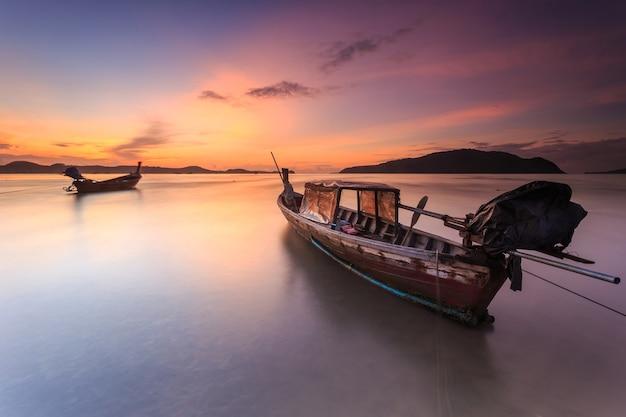 Traditionelles thailändisches boot des langen schwanzes und schöner sonnenaufgang in dem meer in phuket, thailand