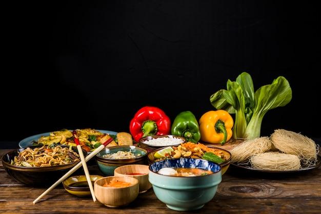 Traditionelles thailändisches essen mit reissuppennudeln; paprika und bokchoy auf schreibtisch vor schwarzem hintergrund