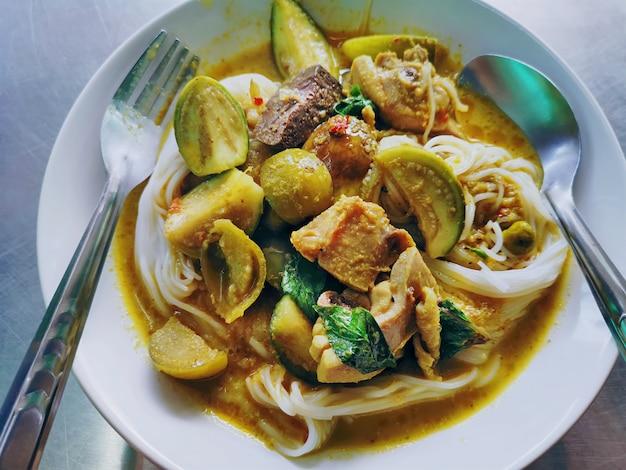 Traditionelles thailändisches essen. reisnudeln mit grünem curry-huhn.