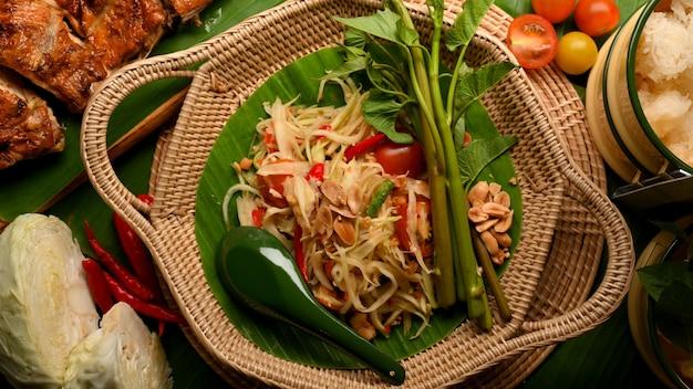 Traditionelles thailändisches essen somtum oder papaya-salat mit gegrilltem hühnchen-klebreis und gemüse nach thailändischer art