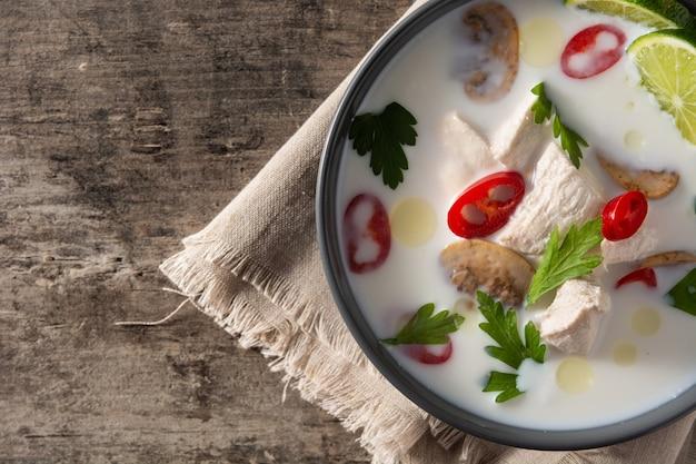 Traditionelles thailändisches essen tom kha gai in der schüssel auf holztisch