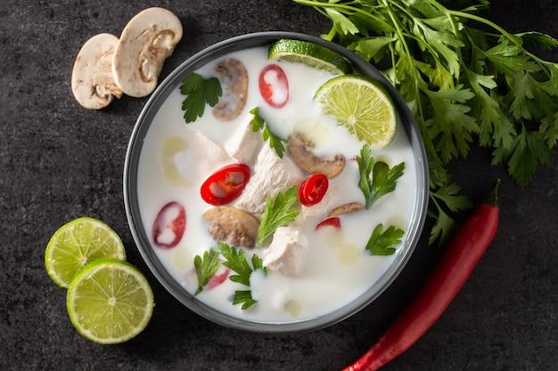 Traditionelles thailändisches essen tom kha gai kokosmilchsuppe mit huhn, ingwer, chilischoten, limette und pilz auf schwarz