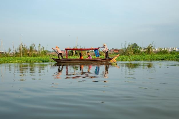 Traditionelles thailändisches gondelboot mit touristen im fluss.