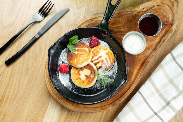 Traditionelles ukrainisches syrniki. pfannkuchen mit quark in einer pfanne mit sauerrahm und marmelade auf einem holzbrett.