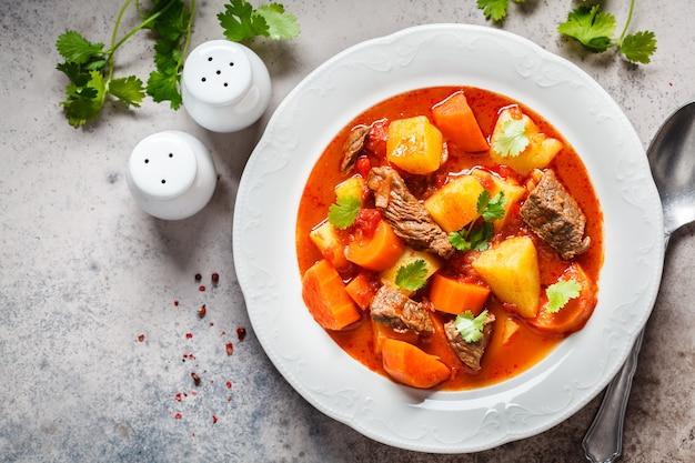 Traditionelles ungarisches gulasch. rindereintopf mit kartoffeln, karotten und paprika in der weißen platte, draufsicht, kopienraum.