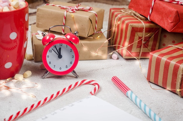 Traditionelles weihnachtsdekorationsgeschenk für baumzweige auf pastellrosa hintergrund flach