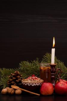 Traditionelles weihnachtsgericht unter den slawen. kerze, äpfel, getränk und kiefer
