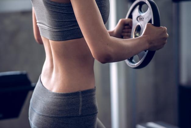 Trägt anhebende gewichte der frau in der sportturnhalle zur schau, bodybuildend und verlieren gewichtskonzept.