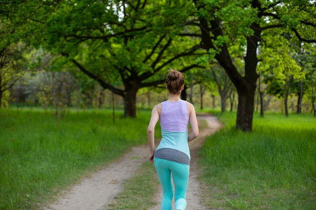 Trägt das brunettemädchen zur schau, das im park rüttelt. grüner wald