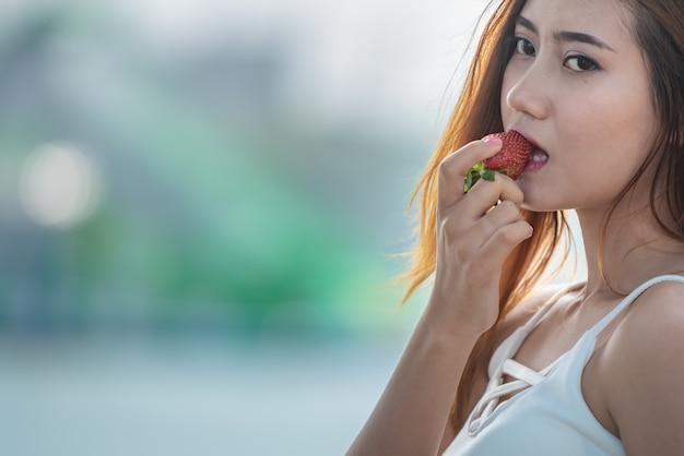 Trägt die asiatische glückliche frau zur schau, die erdbeere isst.