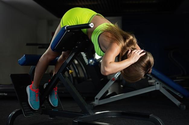 Trägt die junge frau zur schau, die übungen auf rückenmaschine des trainers in der turnhalle tut