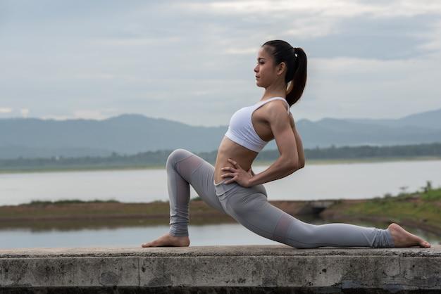 Trägt die jungen frauen zur schau, die morgens yoga durch das reservoir mit gebirgshintergrund üben.