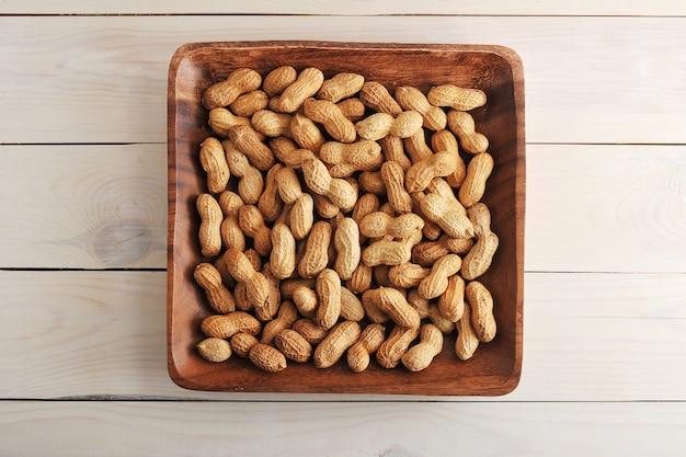 Trägt erdnuss mit oberteil in der hölzernen platte früchte