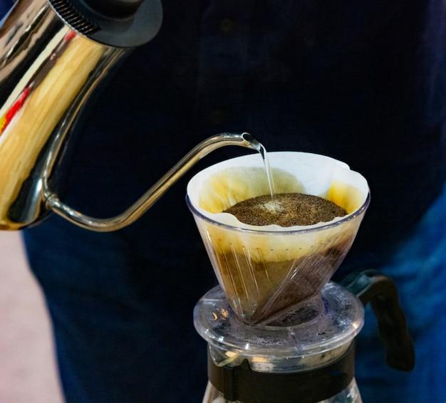Tränken sie das kaffeebrühen, barista gießt wasser auf kaffeesatz mit filter