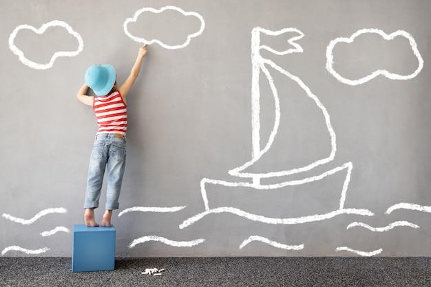 Träume groß! glückliches kind, das im freien spielt. lustiges kind zeichnet ein kreidemeer an die wand. kinderträume vom reisen. kind gibt vor, kapitän zu sein. kinderphantasie und sommerferienkonzept