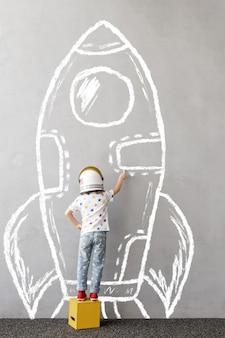 Träume groß! glückliches kind, das im freien spielt. lustiges kind zeichnet eine kreiderakete an die wand. kind träumt vom weltraum. kind gibt vor, astronaut zu sein. kindertraum und fantasiekonzept