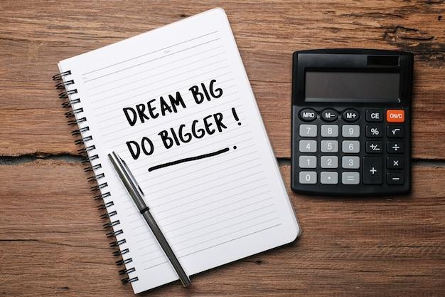 Träume groß machen größer, textwörter typografie geschrieben auf buch vor holzhintergrund, leben und geschäft motivierend inspirierendes konzept
