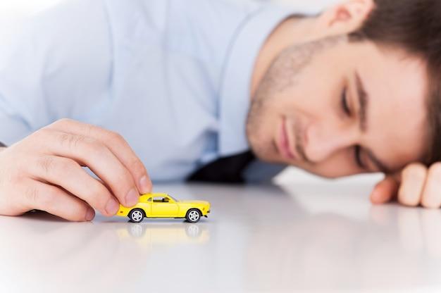 Träume von einem sportwagen. fröhlicher junger mann in hemd und krawatte, der mit spielzeugfahrzeug spielt, während er an seinem arbeitsplatz sitzt