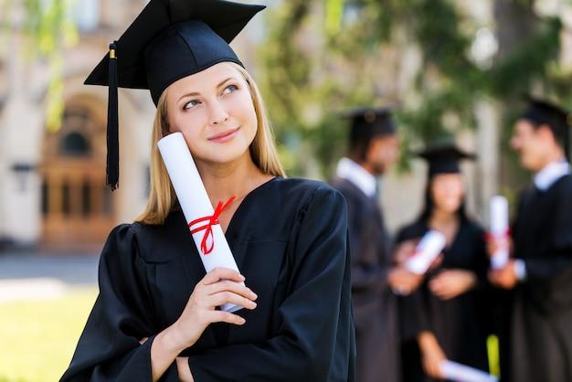 Träume von einer strahlenden zukunft. nachdenkliche junge frau in abschlusskleidern, die diplom hält und wegschaut, während ihre freunde im hintergrund stehen