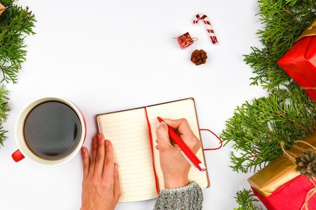 Träume von zielen pläne machen eine liste für das schreiben von neujahrs-weihnachtskonzept in notizbuch