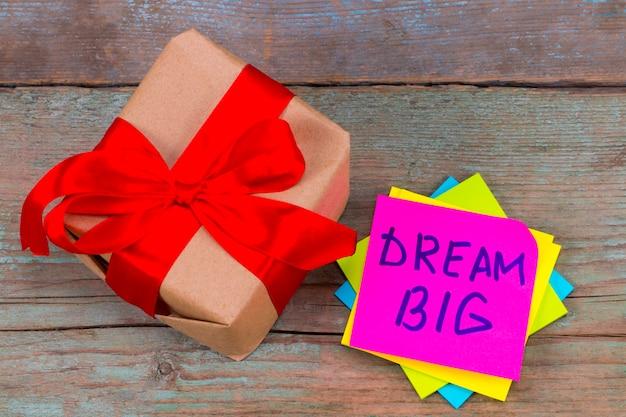 Träumen sie groß und geschenkbox-konzept - motivierende ratschläge oder erinnerung auf bunten haftnotizen.