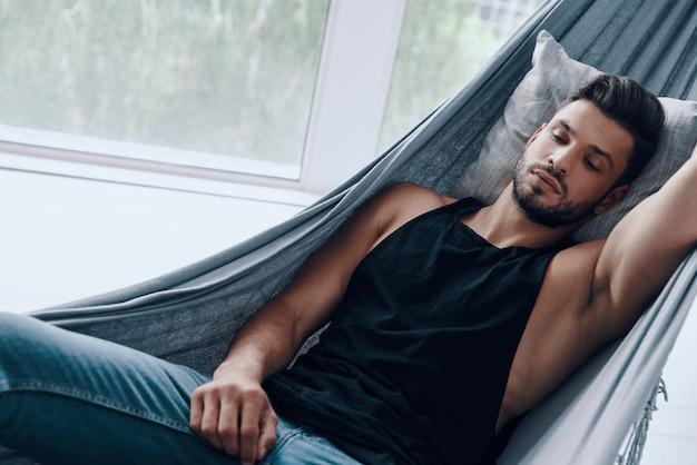 Träumend. blick von oben auf den hübschen jungen mann in freizeitkleidung, der schläft, während er drinnen in der hängematte liegt