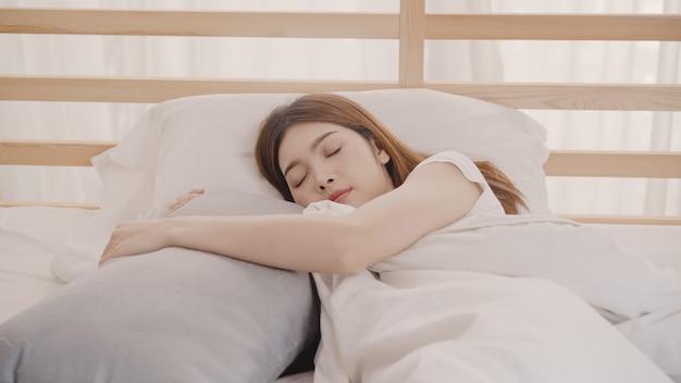 Träumende asiatin beim schlafen auf bett im schlafzimmer