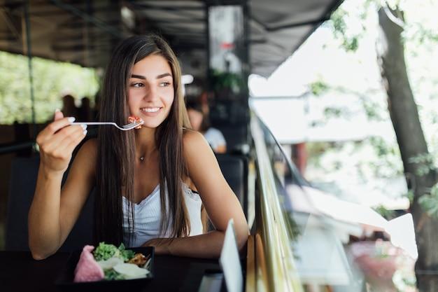 Träumende frau, die gesundes essen isst, das im schönen innenraum sitzt
