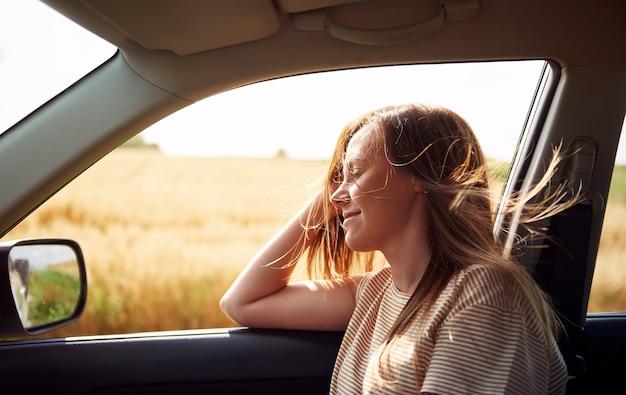 Träumende frau, die mit dem auto reist
