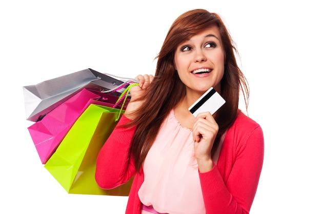 Träumende frau mit einkaufstüten und kreditkarte