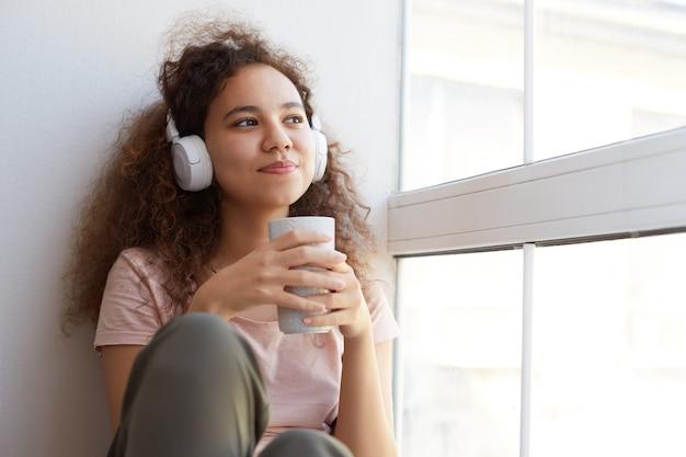 Träumende junge afroamerikanerin mit lockigem haar, hört lieblingslied an kopfhörern und trinkt tee, schaut zum fenster und genießt sonnigen tag zu hause.