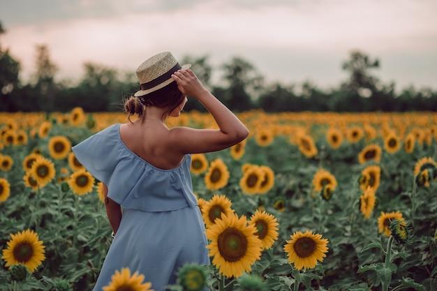 Träumende junge frau im blauen kleid, die einen hut mit einer hand hält und im sommer in einem feld von sonnenblumen weggeht, blick von ihrem rücken. zur seite schauen. speicherplatz kopieren