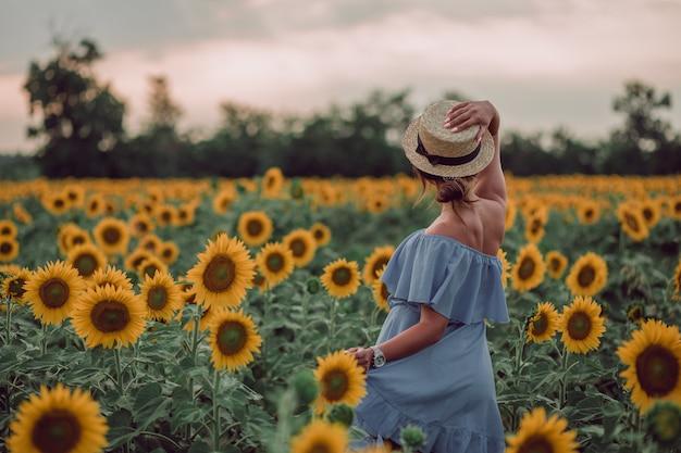 Träumende junge frau im blauen kleid, die einen hut mit einer hand in einem feld von sonnenblumen im sommer hält, blick von ihrem rücken. ich freue mich auf. speicherplatz kopieren