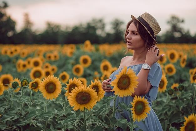 Träumende junge frau im blauen kleid und im hut, die haare mit einer hand in einem feld von sonnenblumen im sommer halten, blick von ihrer seite. zur seite schauen. speicherplatz kopieren